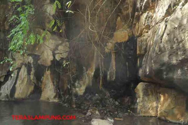 Pancaran air panas yang menyerupai gerojokan keluar dari tebing sungai. Inilah titik kedua sumber air panas di Desa Way Panas.