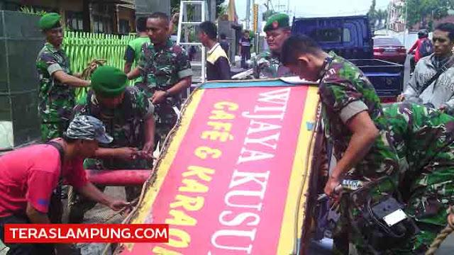 Personel Korem 043 Gatam menurunkan papan reklame tempat hiburan malam Wijaya Kusuma, Senin (14/12/2015).