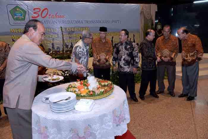 Mantan Menteri Transmigrasi dan Permukiman Perambah Hutan Siswono Yudo Husodo (kiri) memotong tumpeng pada peringatan 30 Tahun Persatuan Wredatama Transmigrasi (PWT) di Balai Makarti Mukti Tama, Jakarta, Selasa (17/5/2016).