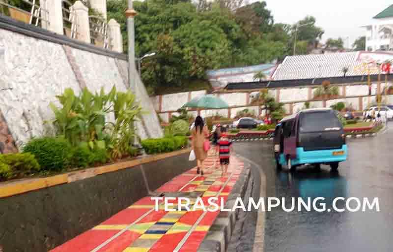 Tanpa payung, Ferdian mengikuti pelanggannya hingga sampai ke tempat angkot yang parkir menunggu penumpang.