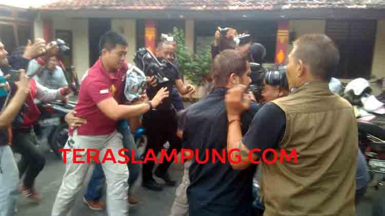 Nizar Romas (RN) menutupi wajahnya dengan koran saat dibawa petugas Polresta Bandarlampung.