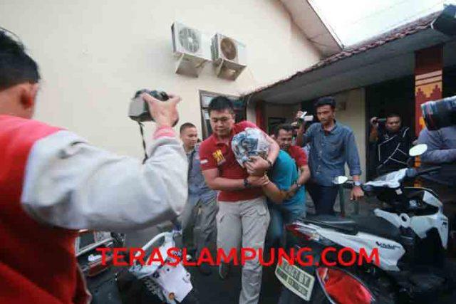 Anggota DPRD berinisial NR terduga pencurian obat-obatan dan alat suntik di RSUAM saat dibawa petugas Satreskrim Polresta Bandarlampung keluar dari ruang pemeriksaan. NR menutupi wajahnya dengan koran.