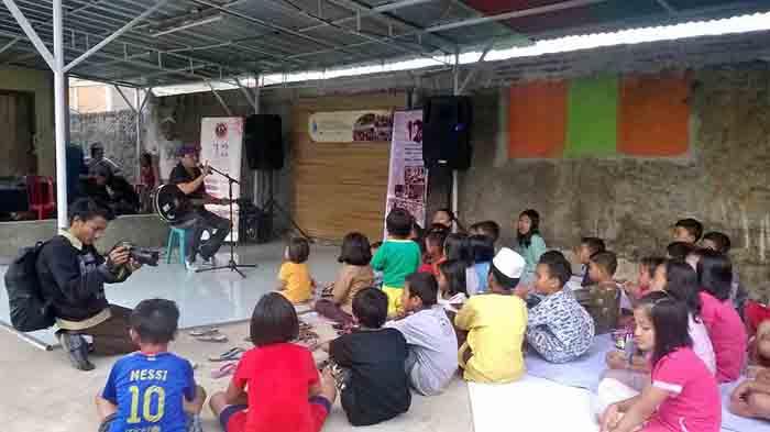 Kim Commanders menyanyi di depan anak-anak Gang Mulya Jaya, Kedamaian, Bandarlampung pada peringatan Hari Anak Nasional, Sabtu sore (23/7).