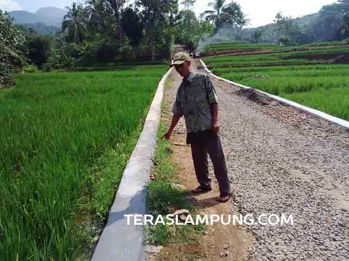 Kepala Desa Gunung Sadar, Abung Tengah, Warta menunjukan TPT yang baru selesa dibangun dengan ADD 2016.