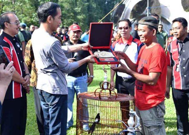 Presiden Jokowi menyerahkan hadiah kepada pemenang dalam acara Festival dan Pameran Burung Berkicau Piala Presiden Jokowi tahun 2018 di Kebun Raya Bogor, Minggu (11/3).