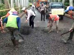 Satuan Lalu Lintas Polres Lampung Utara Bbersama pekerja menambal jalan yang berlubang, Sabtu (26/5/2018).