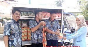 Kepala Bulog Lampung,M.Attar Rizal (paling kiri), bersama karyawan Bulog menunjukkan beras kemasan 200 gram, Kamis (19/7/2018).