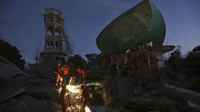 Tim penyelamat mencari korban di puing-puing yang disebabkan oleh gempa di sebuah masjid di Lombok Utara, Senin, 6 Agustus 2018. Data BNPB terakhir menyebutkan, 98 korban meninggal dan 238 luka-luka akibat gempa Lombok. (Foto AP via tempo.co)