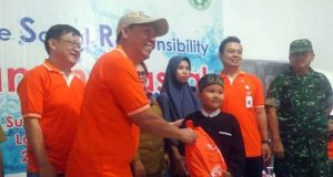 Head of Personal and General Affair and Compliance PT Suri Tani Pemuka Lampung Juhuri Mokodompit memberikan bingkisan kepada anak peserta program khitanan massal.