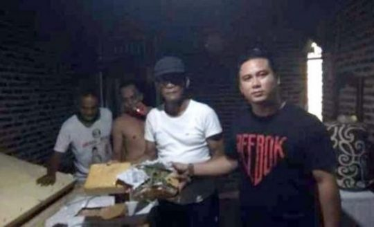 Petugas Ditresnarkoba Polda Lampung (kaos hitam) bersama Kades Natar, Edy Suspondo (kaos putih bertopi) dan warga saat menggeledah rumah kontrakan yang dijadikan tempat untuk menyimpan 400 Kg ganja.