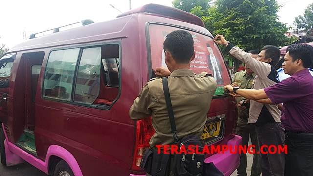 Ketua Bawaslu Kota Bandarlampung Candrawansah bersama pertugas Pol PP melepas banner yang menempel di angkot jurusan Bandarlampung-Kemiling, Selasa,4 Desember 2018.