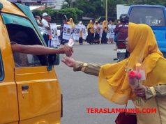 Kader PKS Lampura memberika setangkai bunga kepada pengendara di sekitar Tugu Payan Mas,Kotabumi.