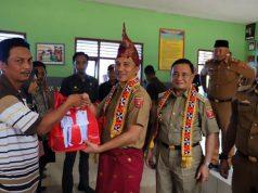 Bupati Parosil Mabsus didampingi Wabup Mad Hasnurin menyerahkkan bantuan seragam sekolah gratis