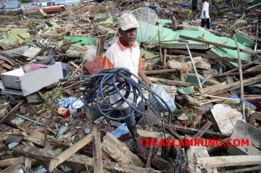 Wahid (50), warga Desa Way Muli saat mengais barang-barang berharga miliknya di reruntuhan bangunan rumah miliknya yang sudah rata dengan tanah