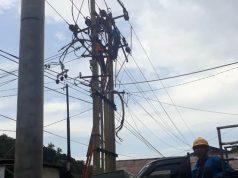 Petugas PLN sedang memperbaiki jaringan listrik.