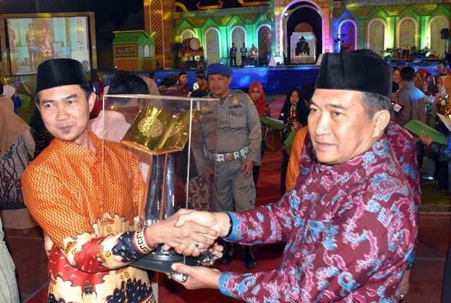 Camat Panjang (kiri) menerima piala untuk Kecamattan Panjang yang sukses meraih juara umum MTQ ke-50 tingkat Kota Bandarlampung 2019.
