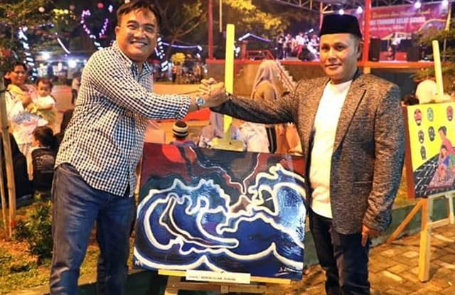 Plt Bupati Lampung Selatan, Nanang Ermanto (kanan), menyerahkan lukisan kepada panitia Malam Amal untuk Korban Tsunami Selat Sunda di Lampung Selatan,Sabtu malam, 19 Februari 2019.