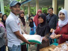 Kepala Seksi Kesejahteraan Rakyat (Kasi Kesra) Desa Suak, Rudi Hartono didampingi pendamping PKH, Siti Nurbaiti saat menyerahkan bantuan non tunai berupa beras dan telur kepada Keluarga Penerima Manfaat (KPM) di Balai Desa Suak.