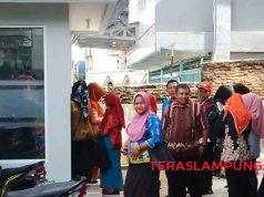 seorang ibu terpaksa duduk karena lelah mengantre di depan ATM Bank Lampung
