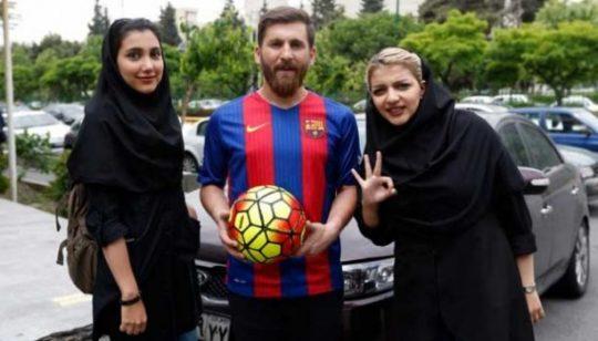 Reza Parastesh, yang memiliki wajah mirip dengan bintang Barcelona Lionel Messi, berfoto dengan warga saat bertemu di jalanan Tehran, Iran, 8 Mei 2017. AFP PHOTO / ATTA KENARE