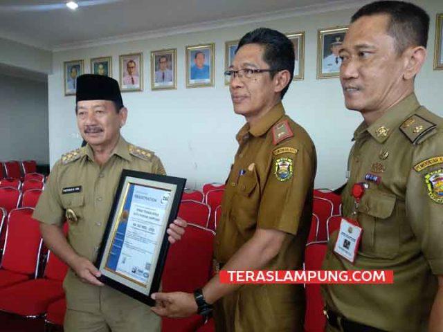 Walikota Herman HN bersama Kadis Tenaga Kerja memamerkan sertifikat ISO 9001.