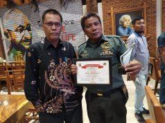 Sertu Zulkarnain menunjukkan piagam Penghargaan Tjindarboemi dari PWI Lampung.