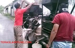 """Suratman alias Temon (kiri) dan rekan kerjanya, Aping saat sedang memproses gabah menjadi beras menggunakan kendaraan mesin penggilingan padi """"Grandong"""" (angkutan) atau Ledok."""
