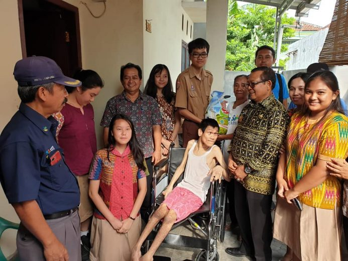 Maruba Siahaan mencoba kursi roda baru sumbangan OSIS SMA Xaverius Bandarlampung.