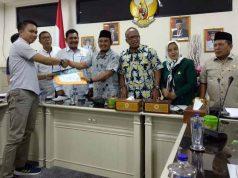 Direktur Walhi Lampung Irfan Musarin menyerahkan berkas tuntutan pencabutan izin PT LIP kepada Ketua Komisi II DPRD Lampun, Wahrul Fauzi Silalahi, Senin (9/12/2019). Foto: Teraslampung.com/Dandy Ibrahim