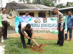 Kapolsek Katibung, Iptu Wido Dwi Arifiya Zaen bersama anggota Polsek Katibung, aparatur desa dan warga setempat saat melakukan penanaman pohon penghijauan.