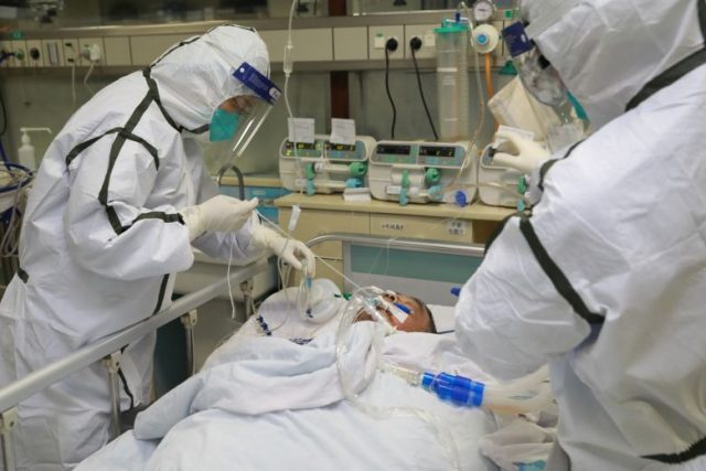 Staf medis dengan pakaian pelindung yang terturup rapat merawat pasien pneumonia yang disebabkan oleh virus corona di Rumah Sakit Zhongnan, Universitas Wuhan, China, Senin, 27 Januari 2020. Foto: REUTERS via The Straits Times