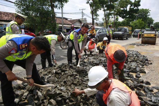 Petugas Sat Lantas Polresta Bandarlampung dan petugas PU Bandarlampung menimbun jalan berlubang di Jl Ryacudu Bandarlampung, Kamis (30/1/2020).