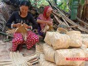 Mbah Maniyem (56) dan anak perempuannya, Yulianti (26) sedang menganyam bilah bambu untuk dijadikan wadah perabot rumah tangga berupa tompo yang biasanya digunakan untuk mencuci beras di samping halaman rumahnya di Dusun Ponorogo, Desa Sidorejo, Kecamatan Sidomulyo, Lampung Selatan, Sabtu (1/2/2020).