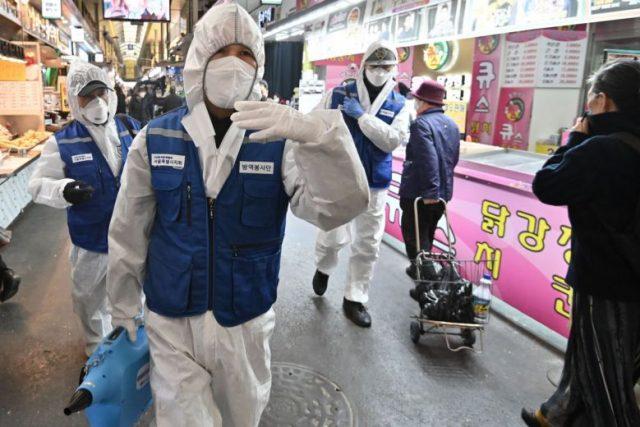 Pekerja dari Asosiasi Pengendalian Hama Korea, mengenakan alat pelindung, semprotan desinfektan untuk membantu mencegah penyebaran coronavirus di sebuah pasar di Seoul pada 24 Februari 2020. Foto: AFP via Straits Times