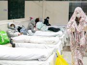 Sebuah foto yang diambil pada 5 Februari 2020, menunjukkan seorang pasien (kanan) ditutupi dengan sprei di sebuah pusat pameran yang diubah menjadi rumah sakit di Wuhan. Foto: AFP via Straits Times