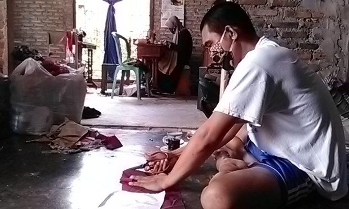 Mbah Yati bersama anak menantunya bernama Sugiarto, tengah mengerjakan pesanan masker yang dibuat dari aneka jenis kain perca.
