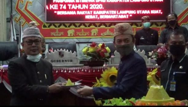 Ketua DPRD Lampung Utara, Romli memberikan potongan tumpeng kepada perwakilan Pemprov Lampung yang hadir dalam sidang paripurna HUT Lampung Utara
