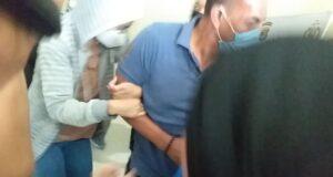 VS (sweater garis) menghindari kejaran para jurnalis di Mapolresta Bandar Lampung, Rabu (29/7/2020). VS diduga terlibat kasus prostitusi online. Foto: kompas.com