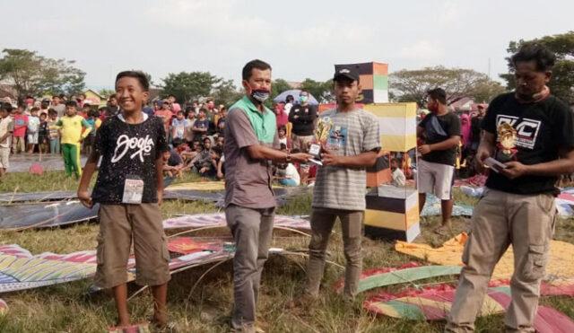 Kepala Desa Sidorejo, Tommy Yulianto didampingi Ketua panitia lomba layang-layang, Budi Santoso atau Hasan menyerahkan hadiah berupa uang tunai dan tropy kepada pemenang lomba, Kamis (23/7/2020) sore.