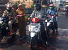 Pegawai Dinas Koperasi dan UMKM Kota Bandarlampung membagikan masker ke pengendara motor di Tugu Adipura, Senin (13/7/2020).