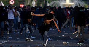 Pengunjuk rasa melempar batu ke arah polisi saat unjuk rasa menolak Undang-undang Cipta Kerja di depan Gedung Negara Grahadi, Surabaya, Jawa Timur, Kamis 8 Oktober 2020. Aksi yang dikuti ribuan orang dari berbagai elemen mahasiswa dan buruh tersebut berakhir ricuh dan mengakibatkan sejumlah fasilitas umum rusak. ANTARA FOTO/Zabur Karuru