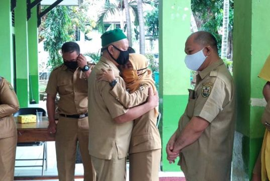 Acara temu pisah Kepala SMPN 16 Kota Bandarlampung yang dipenuhi Isak tangis. Kepala SMPN 16 Purwadi (peci hijau) dirangkul salah seorang guru yang merasa kehilangan.