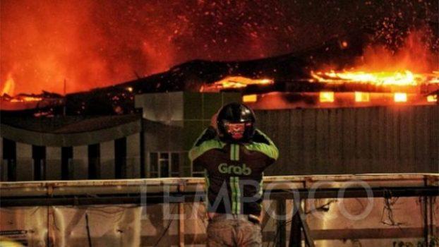 Seorang pengendara ojek online melihat Gedung bioskop Grand Theatre Senen yang terbakar saat terjadinya aksi massa tolak UU Cipta Kerja, Jakarta, Kamis, 8 Oktober 2020. Tempo/Hendartyo Hanggi