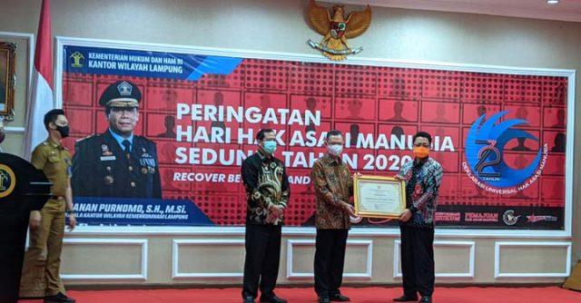 Asisten Bidang Pemerintahan dan Kesejahteraan Rakyat (Kesra) Kota Bandarlampung, Sukarma Wijaya (kanan), menerima piagam Kota Peduli HAM, di Aula Kanwil Kemenkum HAM di Bandarlampung, Senin (14/12/2020).