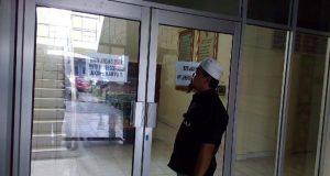 """Seorang wartawan terpaksa menunggu di depan pintu masuk Kantor Bappeda Lampung Utara, Selasa (5/1/2021), karena akses jalur utama masuk telah dipasangi pintu elektronik. Hanya """"orang dalam"""" yang bisa masuk."""