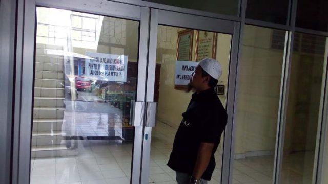 Seorang wartawan terpaksa menunggu di depan pintu masuk Kantor Bappeda Lampung Utara, Selasa (5/1/2021), karena akses jalur utama masuk telah dipasangi pintu elektronik. Hanya