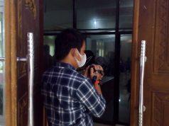 Akibat dilarang masuk, salah seorang terpaksa mengabadikan momen Rakor Pemkab Lampung Utara dari luar aula .