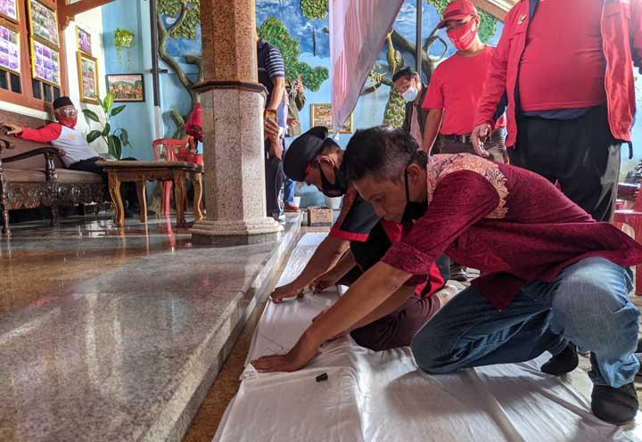 Koordinator Koar Bandes Nuryono (pakai blangkon) didampingi Sahrulsyah menandatangani kain kesetiaan kepada Paslon nomor tiga Eva Dwiana – Deddy Amarullah.