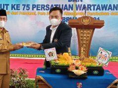 Ketua PWI Lampung Utara, Jimi Irawan memberikan potongan tumpeng pada Bupati Budi Utomo dalam perayaan HPN
