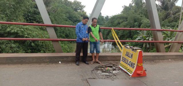 Sekretaris Dinas PUPR Lampung Utara, Rohim Fauzi memasang rambu penanda pada jembatan Way Rarem di Jalintengsum yang rusak parah.